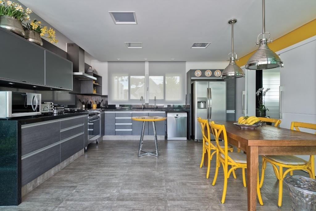 A cozinha se comunica com a sala de jantar pela porta de correr (à dir.). O piso cerâmico (Portobello) imita concreto e cria a base do espaço com predomínio dos tons cinzentos, inclusive nos móveis planejados em MDF (Florense). Para quebrar a seriedade do ambiente, toques de amarelo que aquecem o espaço e aguçam o apetite. O projeto desta casa paranaense é da arquiteta Carla Kiss