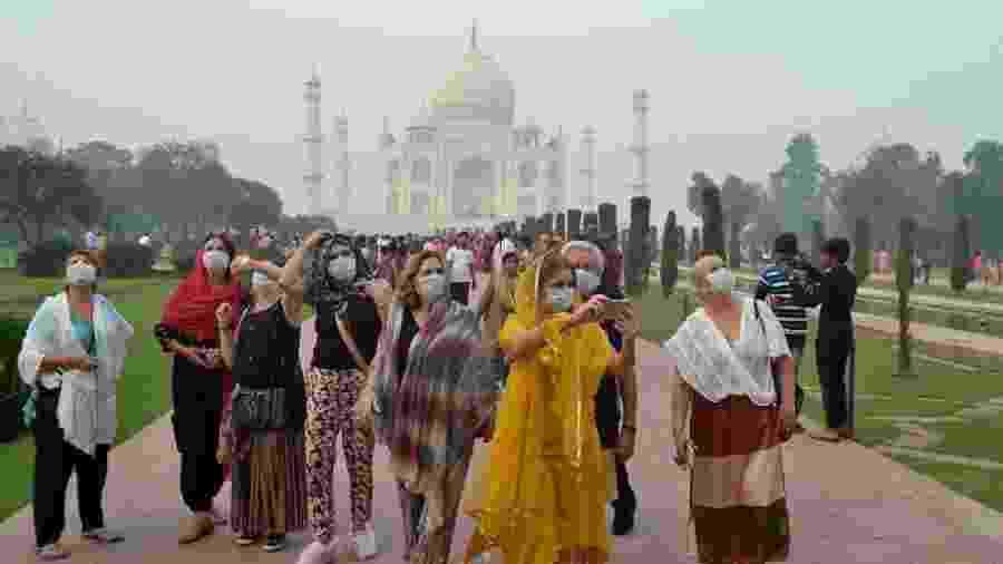 Turistas usam máscaras em visita ao Taj Mahal, em Agra, na Índia - Pawan Sharma/AFP