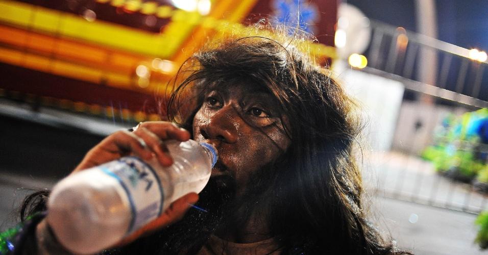 6.fev.2016 - Integrante da Unidos de Vila Maria bebe àgua na despersão do desfile da madrugada deste sábado