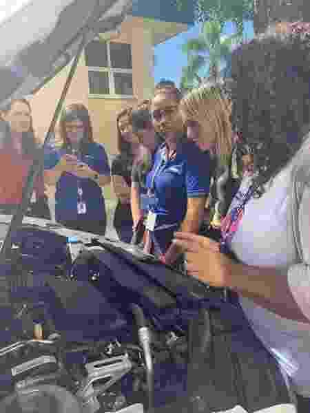 Tainná Santos (de camiseta branca, à dir.), durante aula sobre o funcionamento do motor de um carro - Arquivo pessoal