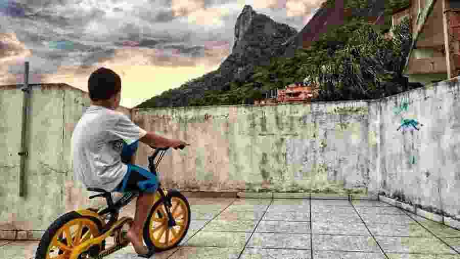 Foto de Elana Paulino na comunidade de Santa Marta mostra menino andando de bicicleta e o Corcovado ao fundo - Arquivo Pessoal
