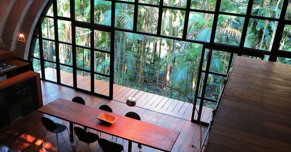 Esse ângulo mostra o interior da Casa Arca, projetada pelo arquiteto Marko Brajovic: a partir do topo, é possível ver a estrutura de madeira (à dir.) que veda os quartos e garante privacidade. Avista-se ainda o terraço estreito próximo à copa das palmeiras