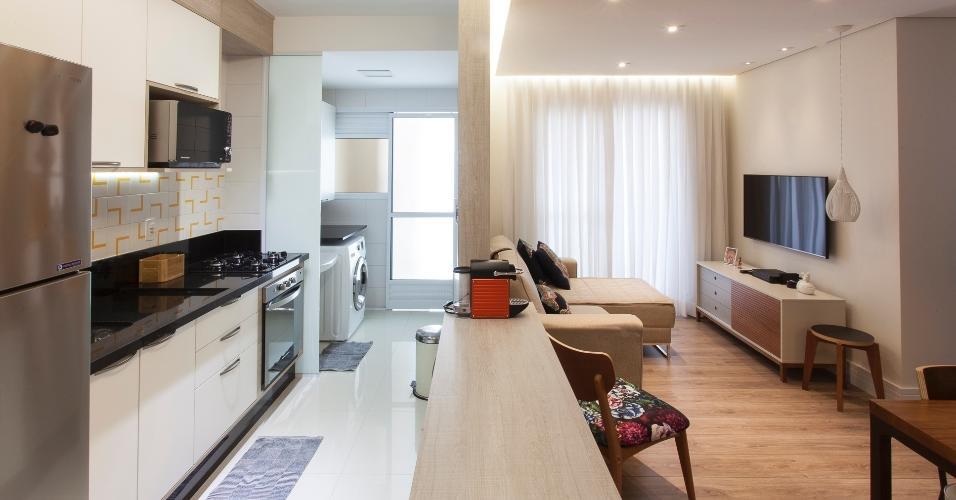 5,70 m². Para aproveitar ao máximo o espaço da cozinha, o pé-direito não foi rebaixado, possibilitando que os armários ganhassem mais altura. O mesmo piso branco está em cozinha e lavanderia, dando a sensação de continuidade e amplitude às áreas. Projeto de Tassia Pereira.