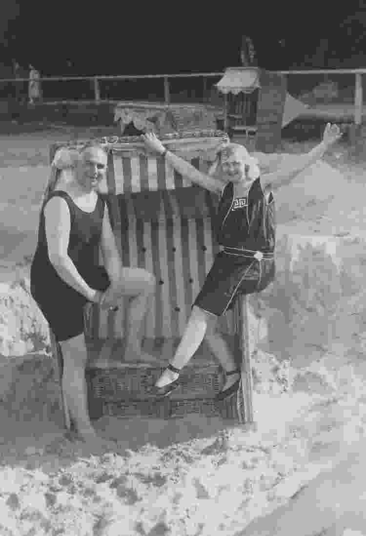 Alemanha, férias de verão de 1924 no Mar Báltico, casal com roupas de banho em uma cadeira de praia - Ullstein bild via Getty Images - Ullstein bild via Getty Images