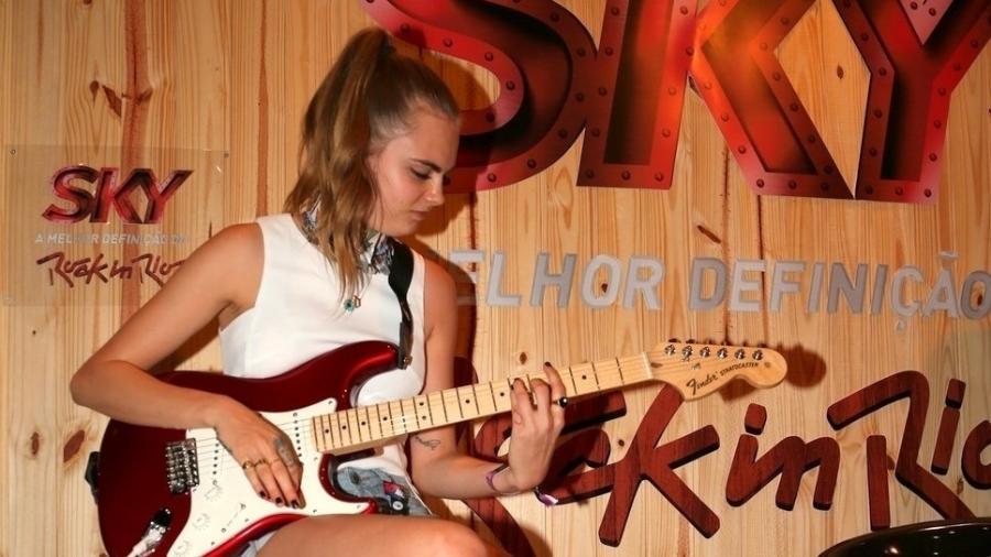 26.set.2015 - Cara Delevingne toca guitarra Fender em camarote do Rock in Rio - AgNews