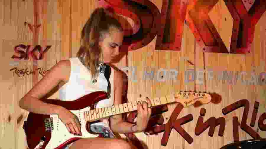 26.set.2015 - Cara Delevingne toca guitarra Fender em camarote do Rock in Rio - AgNews