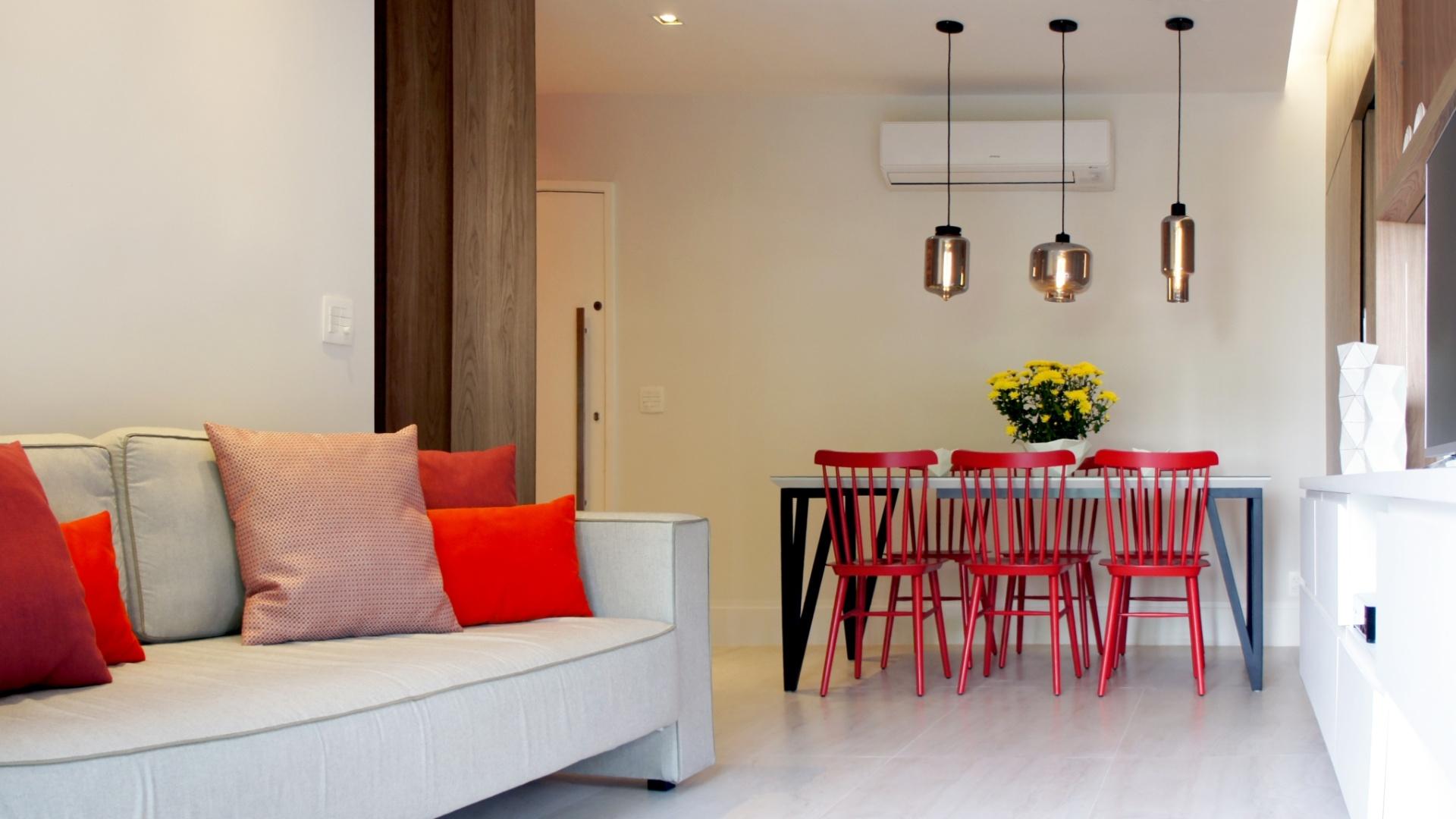O estar é integrado com o jantar pelo piso de porcelanato (60 cm x 120 cm) padrão Travertino Navona, da Portobello, e pelas pinceladas coloridas nas almofadas e nas cadeiras em estilo
