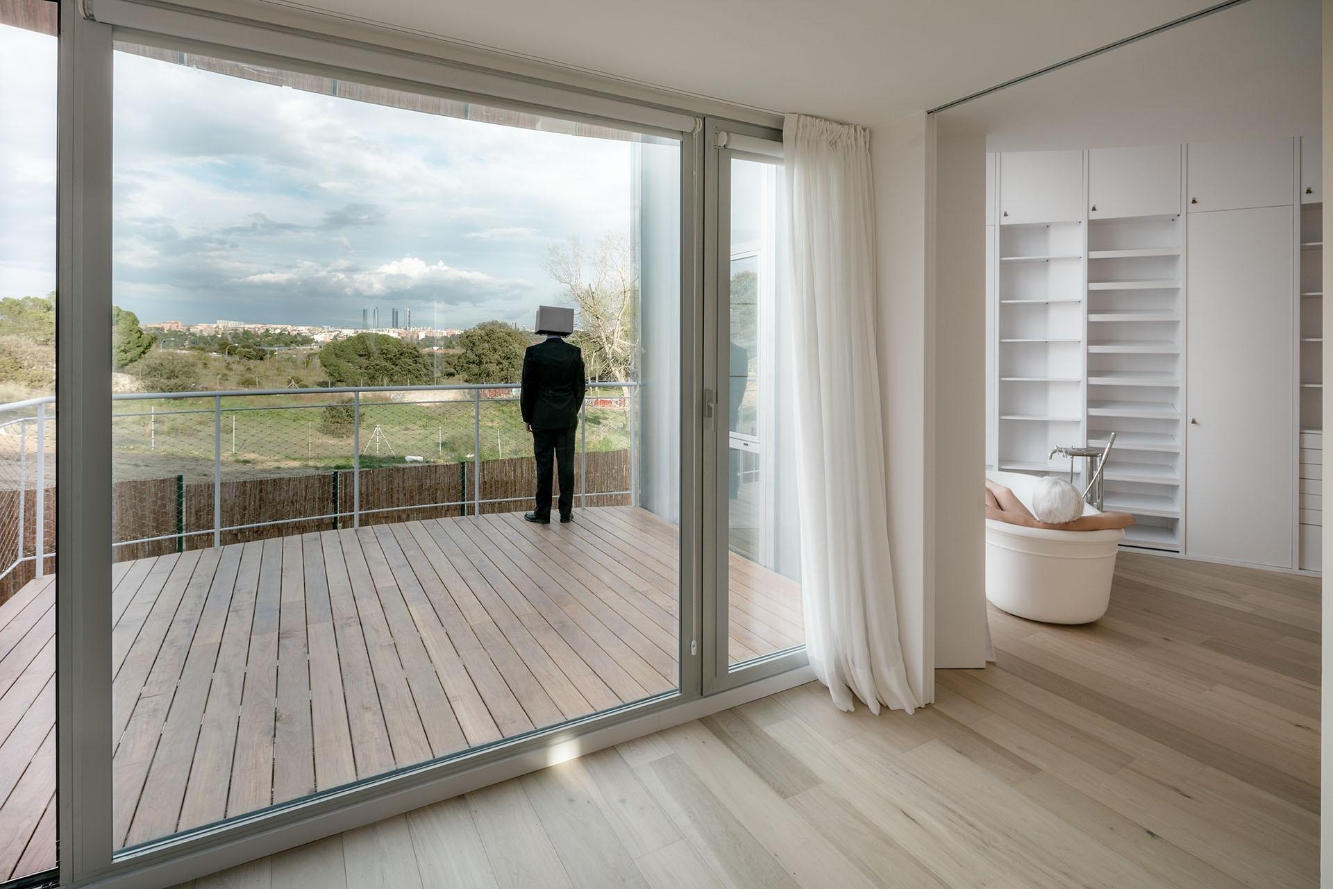 Na área para banhos de imersão, as paredes revestidas de armários são interrompidas e dão lugar a grandes esquadrias (janelas verticais e portas de correr), que se abrem para um terraço-deck. A ideia é aproveitar ao máximo a paisagem de formações arbustivas de pequeno porte e gramíneas de Madri, na Espanha. A casa Tobogan é assinada pelo escritório Z4Z4 Architects