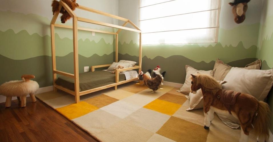 O dormitório do Bento foi inspirado na fazenda dos avós, no Mato Grosso do Sul, e conta até com galinhas e cavalos de brinquedo. Para criar um ambiente ainda mais aconchegante, a blogueira Lucila Turqueto fez desenhos a mão livre na parede e criou um degradê esverdeado. A estrutura em forma de casa, sobre a cama, é outro detalhe charmoso do quartinho