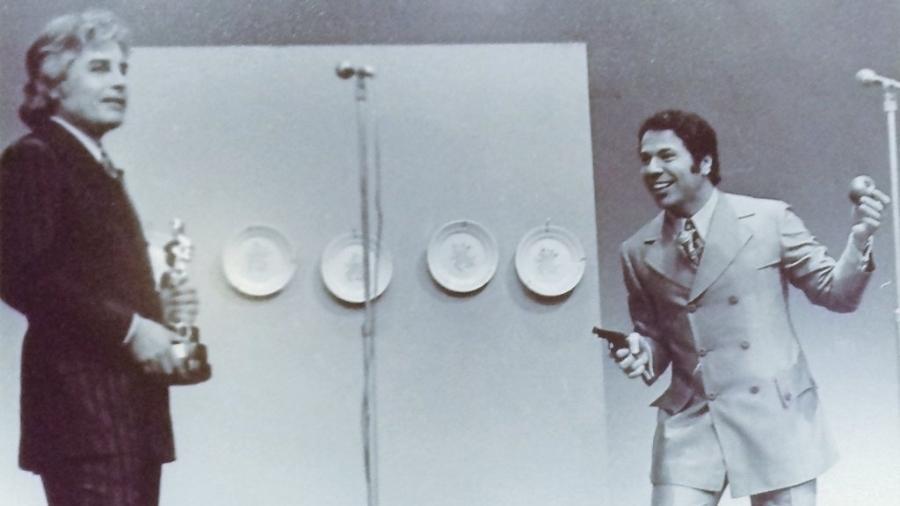 """Silvio Santos aponta revólver para Cid Moreira no """"Troféu Imprensa"""" (1973) - Reprodução/MIS"""