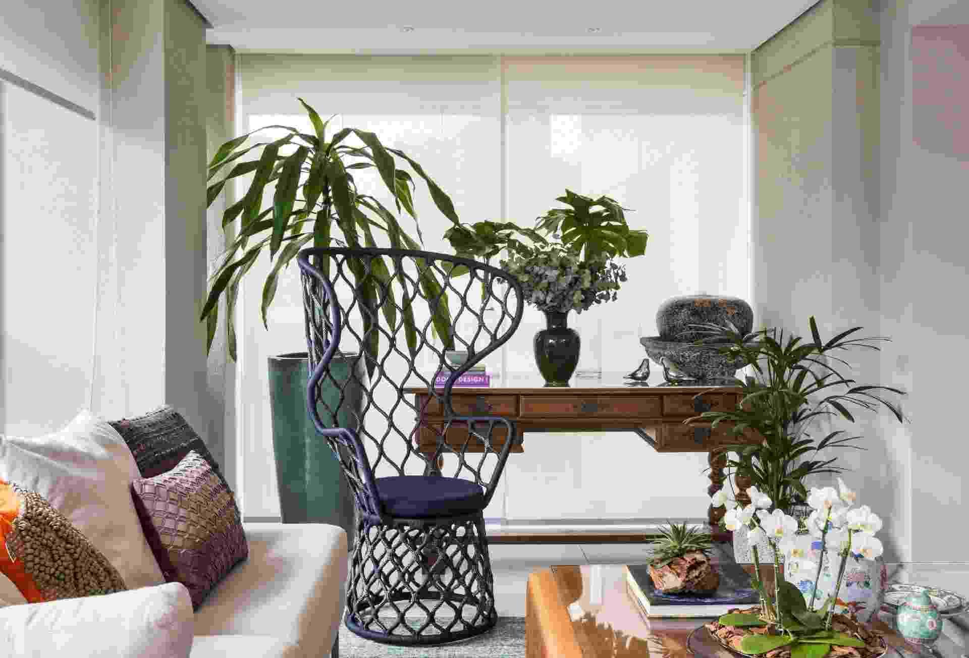 Na varanda integrada à sala de estar, a arquiteta Ana Yoshida não tinha espaço para um generoso jardim, mas a presença de verde era um desejo dos moradores. Entrou em cena a composição de vasos grandes no chão e pequenos sobre os móveis: eles reúnem costela-de-adão, eucalipto, rafia, dracena e as delicadas miniorquídeas - Evelyn Müller/Divulgação