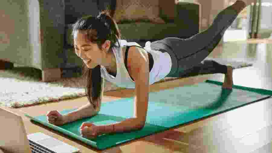 Mulher faz exercício físico em casa vendo aula no notebook: virou rotina em tempos de quarentena - jacoblund/Getty Images/iStockphoto