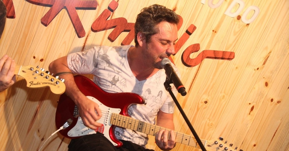 19.set.2015 - Alexandre Nero dá uma palinha na guitarra que acaba de ganhar da produção do Rock in Rio. Enquanto isso, o Metallica no Palco Mundo