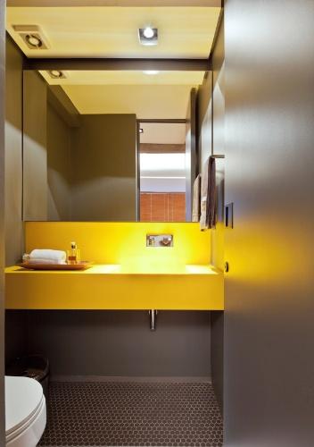 O lavabo do apartamento de 160 m2 no Paraíso, zona sul de São Paulo é inteiramente pintado na cor grafite com destaque para a cuba de quartzo amarela. O arquiteto Renato Dalla Marta, do AUM Arquitetos, também revestiu o piso com uma pastilha hexagonal na cor cinza