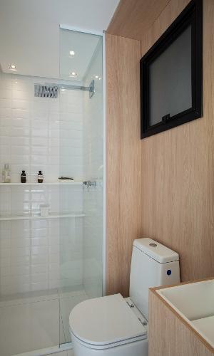 No banheiro, uma parede foi revestida com lâmina de madeira no padrão carvalho, usada em outros pontos do apê com 14 m², e as demais receberam cerâmica.