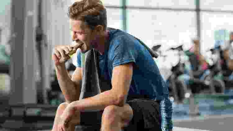 Homem comendo barrinha na academia - iStock - iStock