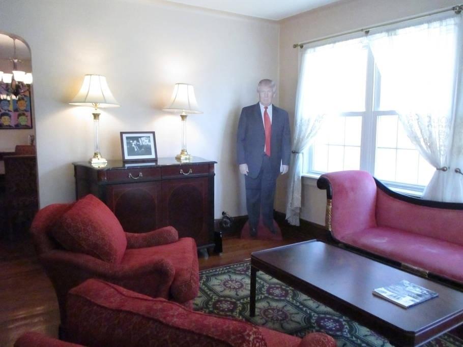 """O diferencial mais atrevido, digamos assim, é que a casa já vem com uma grande fotografia de Trump em papelão, que é deixada na sala e pode """"acompanhar"""" todos os seus passos ali."""
