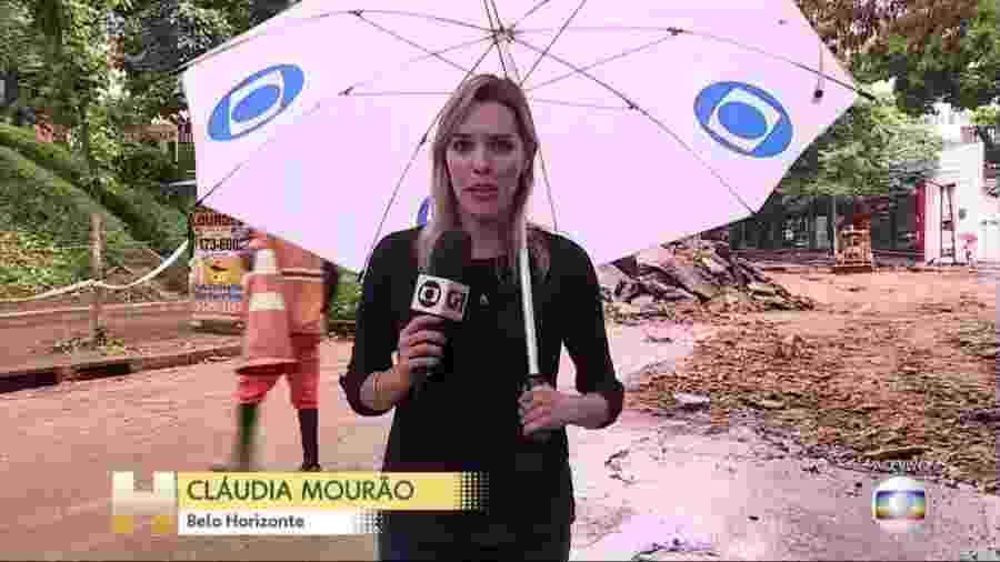 Repórter Cláudia Mourão, sem a menor cerimônia, com microfone numa mão e guarda-chuva na outra - Imagem