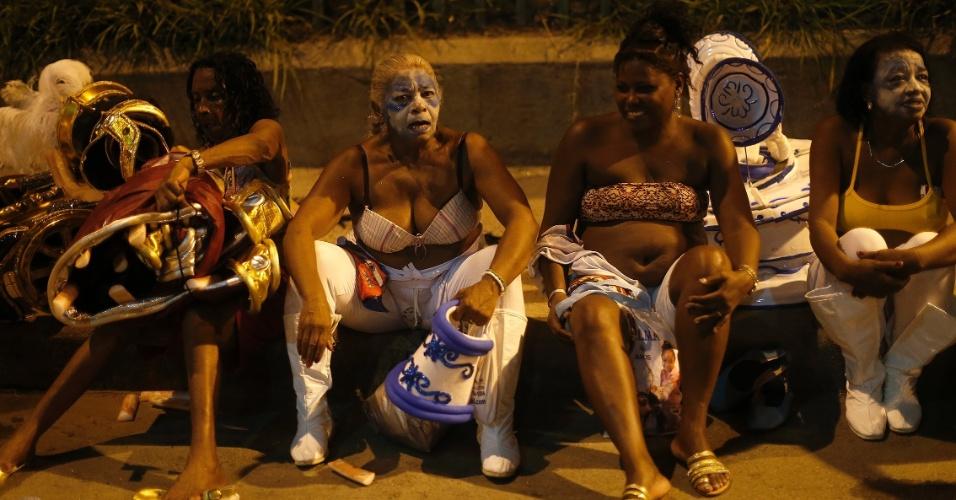 7.fev.2016 - Integrantes das escolas descansam na calçada após desfilarem na Sapucaí