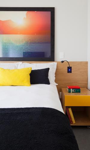 O quarto do rapaz tem visual aconchegante e contemporâneo com superfícies claras, cabeceira de carvalho americano e pinceladas de cor nas almofadas e no quadro. O imóvel pertence a um jovem economista e foi projetado pelos arquitetos do escritório Conrado Ceravolo, em São Paulo