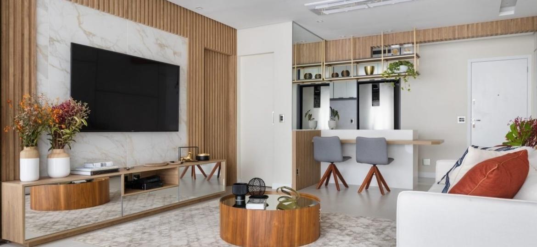 Trazendo sofisticação e amplitude para a sala, o rack espelhado harmoniza com o amadeirado claro presente no painel ripado que emoldura a TV - Fernando Crescenti