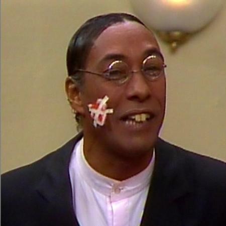 Batista, outro bajulador do Professor Raimundo, interpretado por Eliezer Motta - Montagem/Divulgação/Reprodução/TV Globo