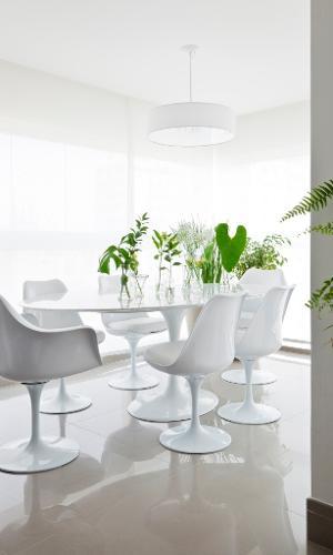 A mesa de jantar Saarinen (1,98 m x 1,22 m) é oval e tem tampo em mármore Carrara e base estruturada em alumínio fundido. Seis cadeiras, também desenhadas por Eero Saarinen, rodeiam o móvel decorado com vasos de vidro e folhas verdes. O pendente é da Reka e o projeto foi assinado pelo escritório Iná Arquitetura