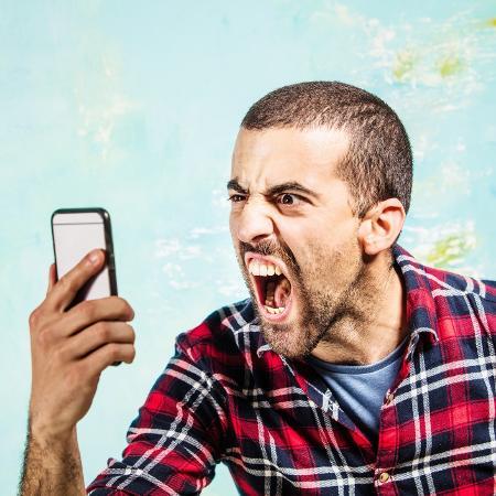 Homem gritando com o celular - Getty Images