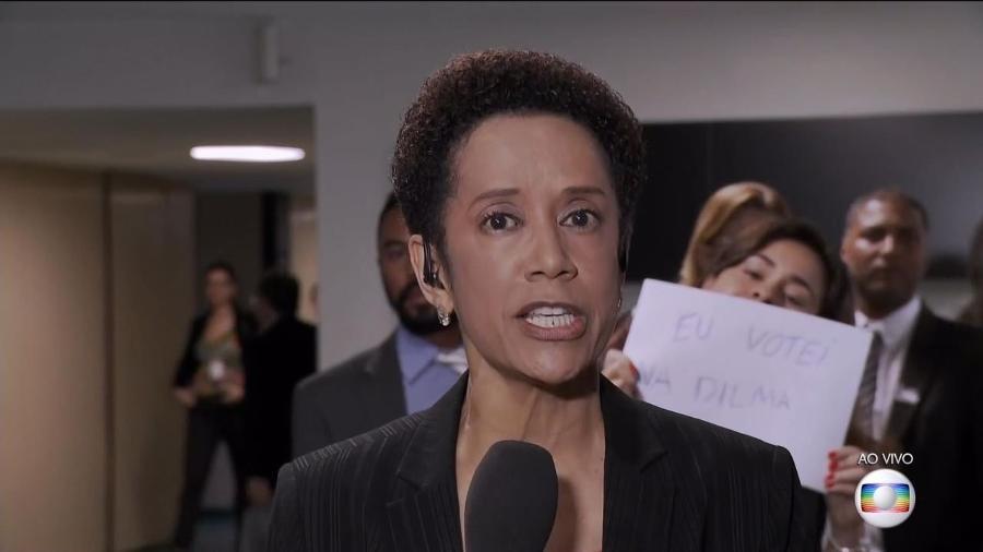 Mulher aparece com um cartaz atrás da repórter no programa ao vivo - Reprodução/TV Globo