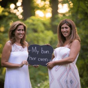 """Irmãs seguram placa divertida com os dizeres: """"Meu pãozinho... No forno dela"""" (em livre tradução)  - Allison Rose Photography"""