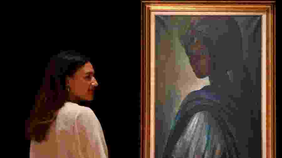 """Mulher observa o quadro """"Tutu"""", de Ben Enwonwu, que é chamado de """"Mona Lisa africana"""" - AFP"""