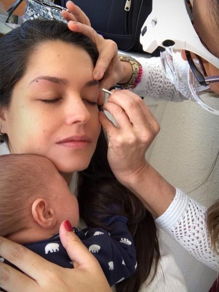 A atriz Thais Fersoza segura o filho, Teodoro, enquanto faz a sobrancelha - Reprodução/Instagram
