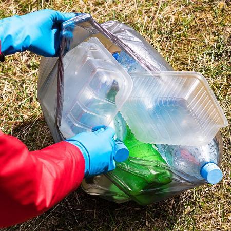 Pessoa recolhe lixo reciclável, plástico - Getty Images/iStockphoto