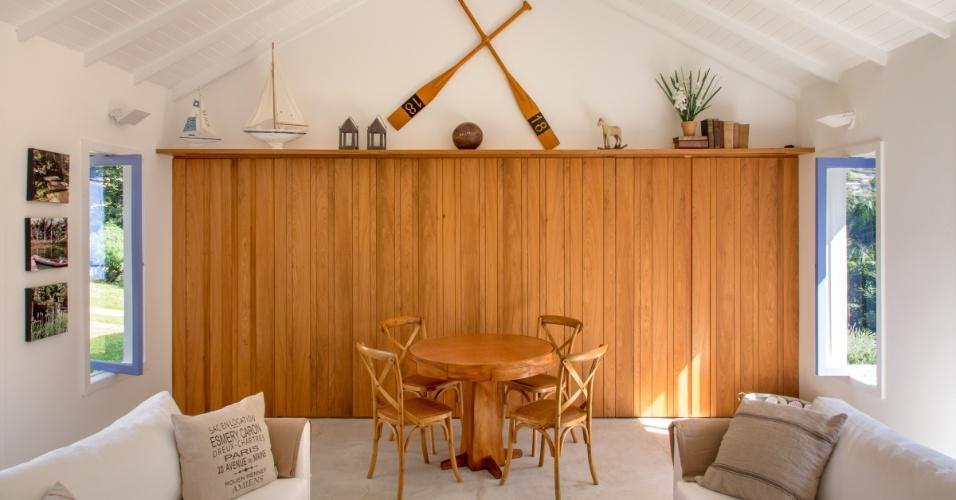 Do ângulo oposto da sala de estar do pavilhão dos filhos, vê-se o espaço para sessões de carteado e um armário em peroba do campo, que ocupa toda a parede. O sítio Marigold tem projeto do arquiteto André Luque