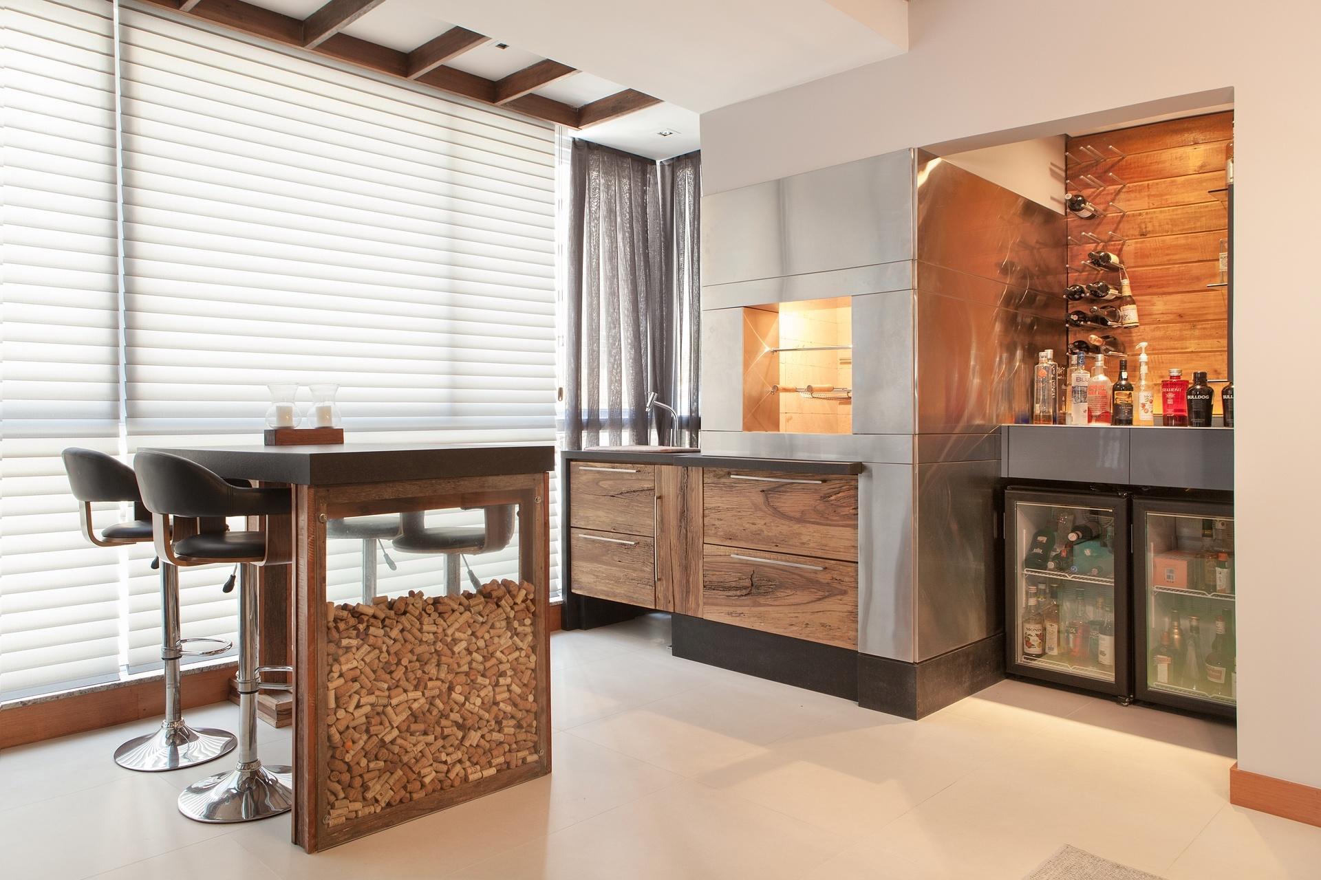 Na sacada, a marcenaria rústica compõe com o aço inox da churrasqueira. O nicho revestido de madeira de demolição acomoda a adega e um pequeno bar. O O Apartamento em Floripa (SC) é projeto é de Pimont Arquitetura