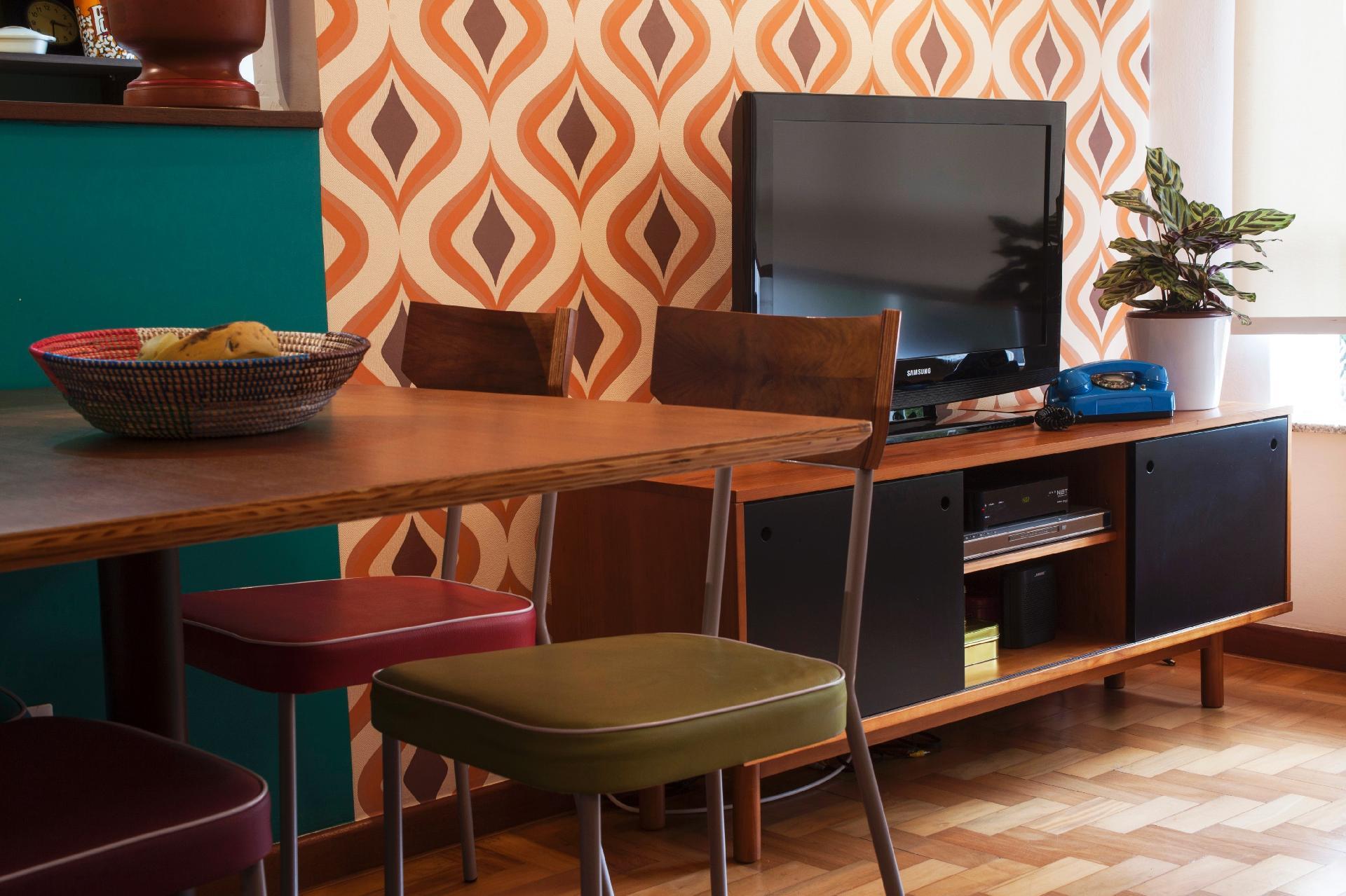 O rack para TV, em madeira (Oppa), também tem inspiração 'retrô' e dá apoio ao antigo telefone de disco, na cor azul celeste. A peça cria um belo contraste com o papel de parede baseado no marrom, no laranja e no