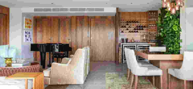 Neste projeto, o painel onde estão as portas mimetizadas desta área social se integraram com a adega de vinhos - Maura Mello