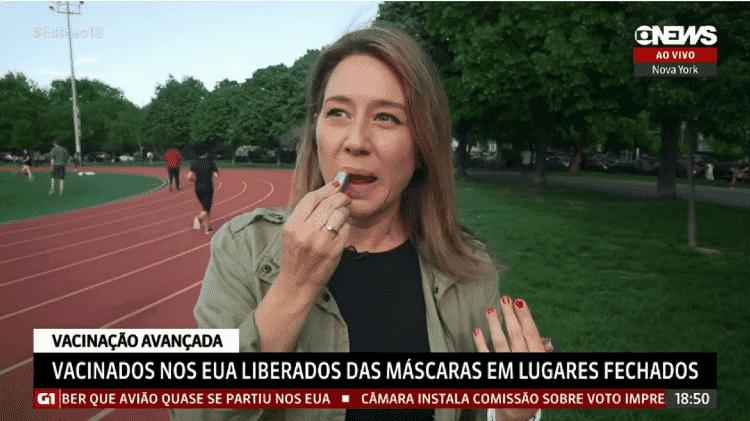 A repórter Carolina Cimenti passa batom em entrada ao vivo na GloboNews - Reprodução/GloboNews - Reprodução/GloboNews