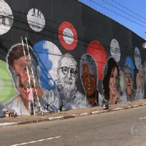 13.ago.2015 - Cinco grafiteiros trabalham na pintura de jornalistas e artistas da Globo em um muro da Marginal Tietê, na Barra Funda, bairro localizado na zona Oeste de São Paulo, próximo à sede da Record, a sua principal concorrente na TV aberta. O trabalho é uma homenagem dos profissionais aos 50 anos da emissora, completados em abril. - Reprodução/TV Globo