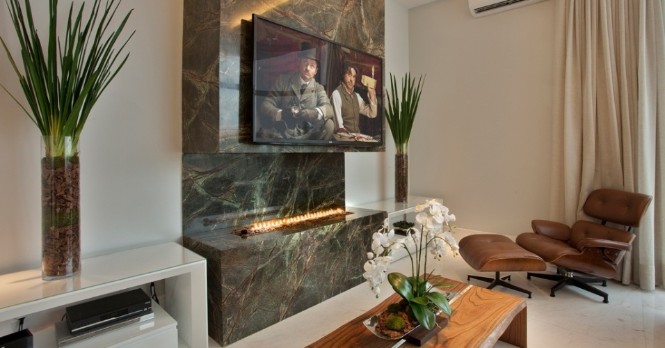 O frontão de mármore funciona de painel de TV e deixa o canto da lareira sofisticado. Dois aparadores laterais arrematam a proposta com elegância e simetria graças ao par de vasos de vidro situados na lateral. Ideia do arquiteto Aquiles Nícolas Kílaris