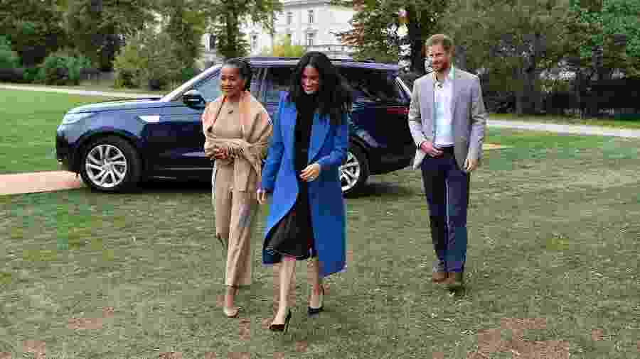 Meghan, a duquesa de Sussex, com sua mãe, Doria Ragland, e o príncipe Harry durante o lançamento do livro de receitas das mulheres afetadas pelo incêndio na torre Grenfell no palácio de Kensington - AFP