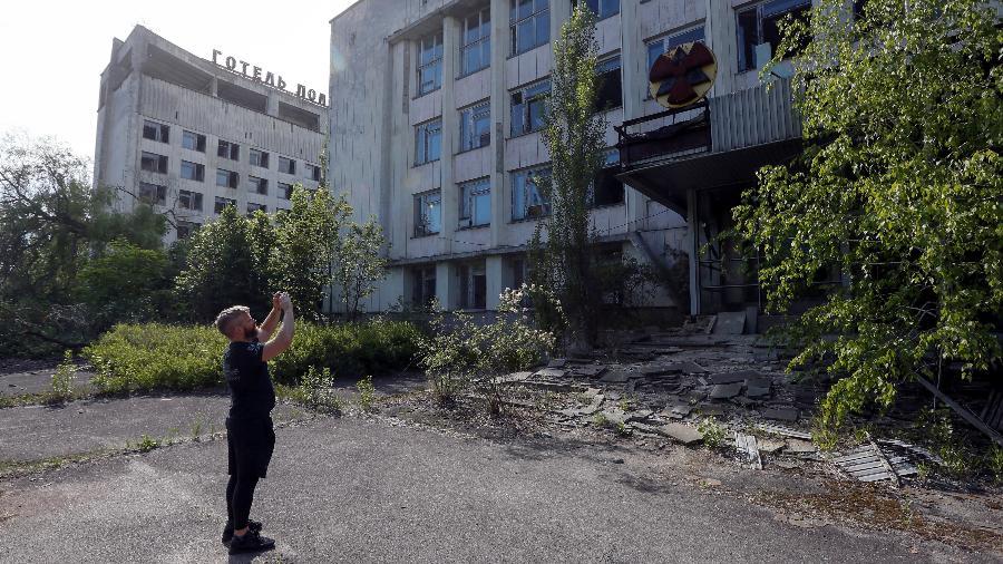 Visitante tira fotos em prédio edifício em Pripyat, próximo à usina nuclear de Chernobyl - Valentyn Ogirenko/Reuters
