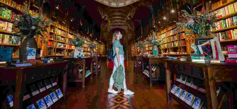Turista com máscara de proteção visita a livraria Lello, ícone de Porto - Getty Images