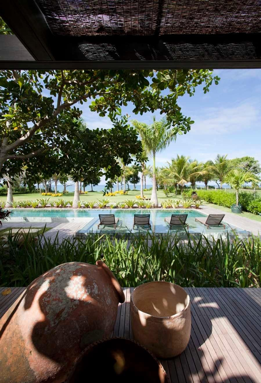 Do deck de madeira da varanda na suíte máster, o casal de moradores pode descansar e usufruir da vista da piscina e do mar de Trancoso (BA). Quem assina a arquitetura da casa Areia é Debora Aguiar