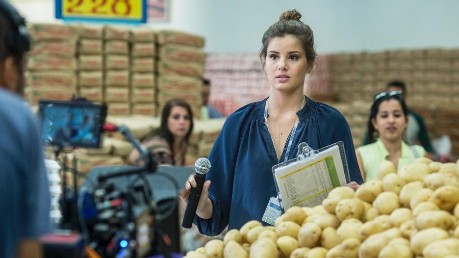 """Luiza (Camila Queiroz) aceita a primeira oferta de emprego que aparece na sua vida depois da família perder toda a fortuna. A ex-milionária vira locutora de supermercado em """"Pega Pega"""" - TV Globo/Maurício Fidalgo"""