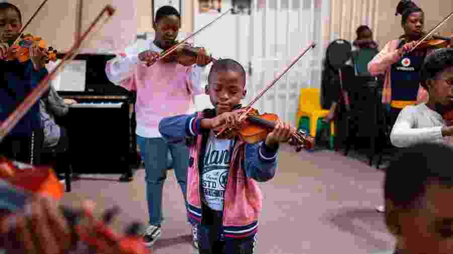 Criança pratica violino em igreja de Soweto, na África do Sul - Wikus de Wet/AFP