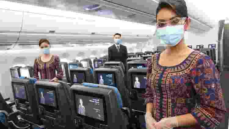 Comissários da Singapore Airlines usam máscara e luvas durante o serviço de bordo na pandemia - Divulgação - Divulgação