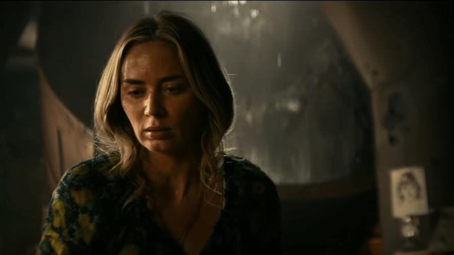 """Emily Blunt em cena de """"Um Lugar Silencioso - Parte 2""""; ao fundo, um dos alienígenas do filme à espreita - Reprodução/YouTube"""