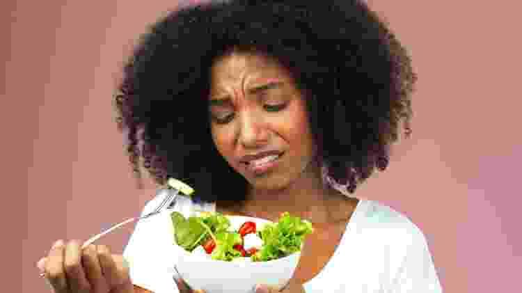 seletividade alimentar, mulher infeliz comendo salada - iStock - iStock