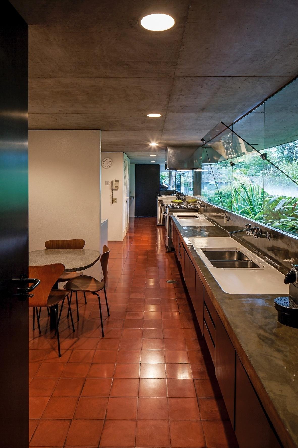 A arquiteta Marlene Milan Acayaba desenhou o mobiliário de cozinha da Casa Milan. O espaço conta com fita de janelas basculantes em vidro, bancada em concreto polido, brilhante, formando uma linha de corredor que chega à porta de acesso direto para a garagem, nos fundos